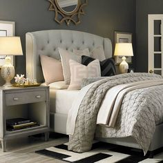 Cozy bedroom with tufted upholstered bed, neutral light grey linens w/ soft pink accents, black and white rug