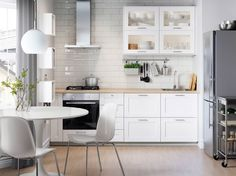A white kitchen with stainless steel appliances and white chairs and a round dining table.