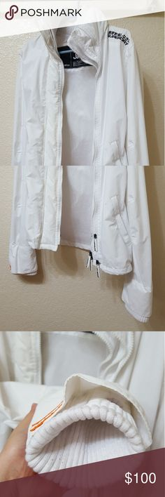 White Superdry windcheater women sz M Worn less than 5 times. Since it is white, the special thumb hole feature the palm area shows wear and minor sweat marks.  This is perfect for spring, summer, and fall (no hood). Pushing it for hard winters. It features 3 sets of zippers, zip all three for that extra warmth sensation. Neck features high sweater like collar, and the exterior has a puffy feel to it as well. The difference between this (windcheater) and other style (windbomber?) The sleeve…