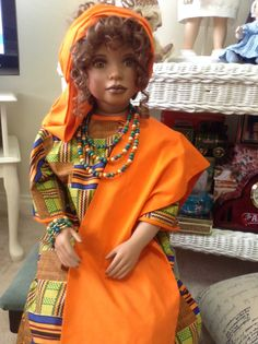 This porcelain doll is called Kenya and the fabric used for her clothes is authentic African fabric.