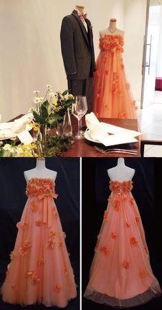 Mia Via FESTA/カラードレス「Juno」。お花のモチーフがたっぷりあしらわれた華やかな衣裳。動くたびに揺れる軽やかな雰囲気と、鮮やかなオレンジ色が花嫁様の可愛らしさを演出してくれます。ゲストと近い距離で和やかに過ごす、アットホームなパーティスタイルにもお勧めです。