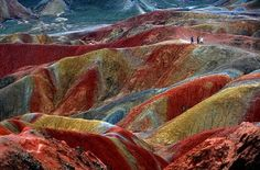 This unique geological phenomenom known as Danxia Landform, can be seen in several places in China.  The color is a result of millions of years of accumulated red sandstone and other sediments which have dried and oxidized.