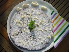 Chocoladetaart, versierd met witte chocoladeschilfers, slagroomtoefjes, munt en witte bloemsuiker