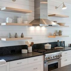 Lining The Kitchen Wall With Shiplap, This Wall Becomes A Farmhouse Styled  Backsplash With Blond Floating Shelves.