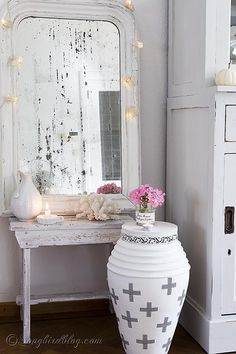 A vintage French mirror, a vase makeover with paint and washi tape and some twinkly lights, create a lovely little corner. http://www.songbirdblog.com
