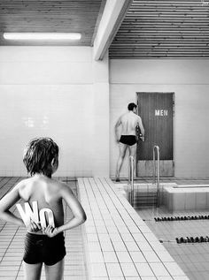 black and white photograph of mischievous little boy.  #swimmingpool