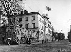 Potilas katsoo Unioninkadun katuvilinää Vanhan klinikan muurilta 1907. Klinikan katolla liehuu Suomen Punaisen Ristin lippu.