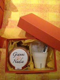 Gianni e Nadia hanno scelto per i loro ospiti un vasetto di Gelatina di More con etichetta personalizzata e una tazzina da caffè e una paletta della linea ESTETICO QUOTIDIANO di SELETTI®. La scatola di colore arancione è stata rivestita al suo interno di carta di riso gialla con fiocco in organza.