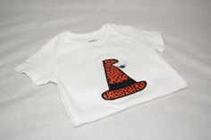 Halloween Witch Hat With Spideris appliqued directly onto a super soft white bib, bodysuit or t-shirt with your child's name embroidered directly below the applique in your choice of font style. Choose from boy's crew neck t-shirt or girl's lettuce edge t-shirt. Leave information in boxes below.