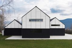 Three dark elongated volume with symmetrical globe roofs definethe exterior of this house designed by Ljubljana-based architecture practice SoNo Arhitekti in an area which represents a typical Slovenian landscape.