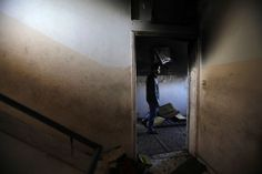 A Palestinian walks inside a burnt house after two little girls Malak and Gana Sheikh el Eid died in it, in Rafah in the southern Gaza Strip March 27, 2014. REUTERS/Ibraheem Abu Mustafa