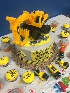 Construction theme cake and cupcakes with toy excavator cake topper