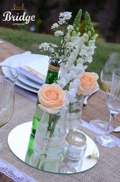 Variar os tamanhos das garrafinhas e tipos de flores cria um efeito lindo na decoração