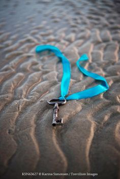 Karina Simonsen KEY WITH BLUE RIBBON LYING ON BEACH Miscellaneous Objects