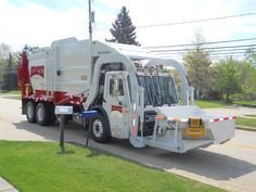 This residential front load truck (aka resi front loader) allows the driver to load trash into the front container, and it's hoisted and emptied into the top of the truck. Some efficiencies may be gained with this truck because the driver doesn't go to the back of the truck at each stop, as is the case for a rear load truck. However, considerations must be made for overhead wires and trees.