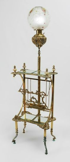 EDWARD MILLER & CO. VICTORIAN PIANO LAMP ETAGERE:  Unmarked attribution, cast brass body with alabaster insert finials on top shelf with 2 mirrored panels over hinged sheet music holder, over lower shelf with 2 mirrored panels.  Shaped legs on 4 feet.  Electrified pierced font with figural cherub masquerons, molded frosted glass shade with cherub masquerons and enamel floral decoration.  Overall to top of chimney 66 3/4'' h. x 18 1/2'' x 12''.