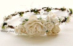 Welcome to Vintage fairy This stunning crown was made with weddings and christenings in mind. The lovely cream and white flowers sit lovely in the front, A gorgeous twist of beads and berries surround the crown with a scatter of tiny blossoms to finish this sweet crown off. Rhinestones are seen nestled within the flowers. Adjustable with ribbon in the back Please specify an age for the perfect fit.Wedding, christening, deb ball, garden party, fairy, dress ups...