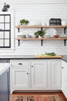 Wraparound iron and wood shelves are mounted on a white subway tile backsplash beside a beside a gray window and above white shaker cabinets painted Benjamin Moore White Dove contrasted with black marble countertops.