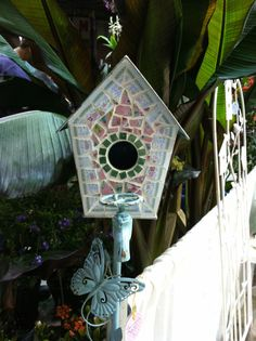 Garden birdhouse stake covered with broken china