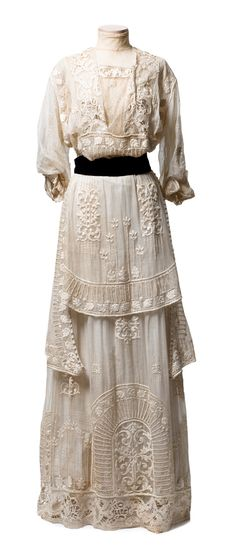 "Embroidered marquisette dress, c. 1910 -- The layers of this magnificent dress are covered with embroidery and lace insertion, and set off with a black velvet ribbon belt. It bears a label: ""Mrs. DeWitt / 5 W. 31st St., N.Y."" It was worn by Cornelia Witsell Farrow Roebling (1866-1942)."