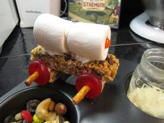 Pioneer Muffin Tin Lunch. Edible covered wagon from granola bar, marshmallows, and lifesavers. Johnny cakes, fruit leather, hand churned butter activity, and trail mix with cow's milk.