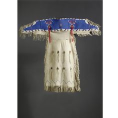 A LAKOTA BEADED AND FRINGED HIDE CHILD'S DRESS    composed of hide, glass beads, silk ribbon and cotton thread.  Length 38 in