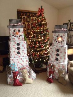 Wrap your presents in white wrapping paper and stack them to look like snowmen! Make the hat using 2 presents wrapped in black paper. Cut out construction paper and glue them to the boxes to make the snowman's face! (Unknown source)