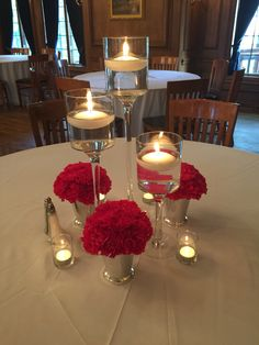 Stemmed floating candle holders with silver julip cups with hot pink carnations