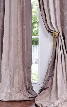 Adding a simple hold back will  let light in and add drama to your drapery panels.