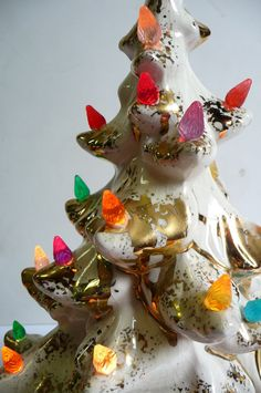 Festive ceramic Christmas tree with stand that lights up and sparkles. White with metallic gold and multi-colored lights. A few bulbs are missing,