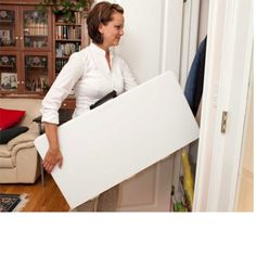 "Lifetime 34"" Square Card Tables - 80273 White Fold-in-Half Folding Table. This picture shows a woman carrying the table."