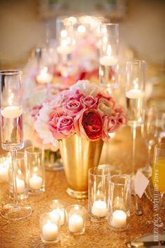Allestimento della tavola con candele galleggianti, vasi oro e fiori rosa e bianchi.