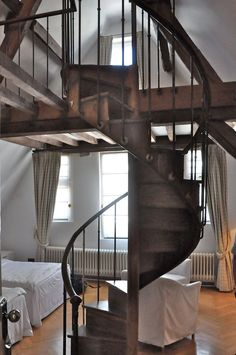 The character of wood and iron spiral staircase leading to a loft