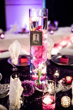 Centerpiece glass cylinders with pink gladiolas. Elegant look for a quinceanera