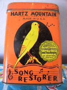 "Vintage ""Song Restorer"" tin bird seed container packaging."