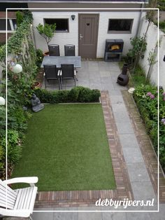 Small backyard garden with bluestone tiles, artificial grass and lots of evergre. Small backyard g