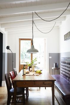 sillas y mesa vintage, sofá de pared y lámparas industriales