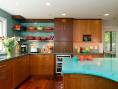 To give this warm, woodsy kitchen an energetic mid-century modern vibe, designer Magued Barsoum chose custom-colored cast concrete for the swoop of island countertop. Backsplash tiles in a similar turquoise tone create the perfect backdrop for a collection of richly hued ceramics.