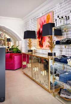 Chic dressing room features an accent wall clad in Queen of Spain Wallpaper lined with a gold antiqued mirrored cabinet, Worlds Away Ponti Antique Mirror With Gold Leaf Entertainment Console, topped with black and gold lamps placed under a pink and red abstract art piece flanked by a hot pink velvet tufted chair to the left and a brass and lucite etagere, Jonathan Adler Jacques Etagere, to the right.