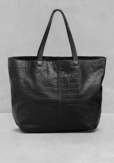 Crafted from smooth leather, this tote features a reptile-embossed surface and small, decorative metal pins below the handles.