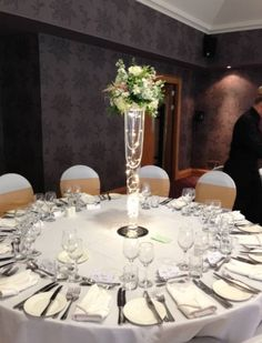 Tall wedding centrepiece - conical vase filled with fairy lights with a mixed flower open arrangement.