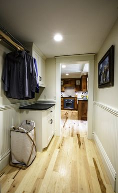 This renovated farmhouse features a laundry room outfitted with white wood, light hardwood floors and a honed black granite countertop. Farmhouse Laundry Room, Farmhouse Remodel, White Farmhouse, Modern Farmhouse, Black Granite Countertops, Light Hardwood Floors, White Wood, Photo Awards, Rustic