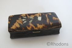 "19th Century Pressed Horn and Tortoiseshell Snuff Box. Rectangular shaped with roller lid. Being made from pressed bone with a nickel metal catch.The lid having an attractive tortoiseshell colored veneer with inlaid brass floral decoration. Believed to date to the mid 1800's Size:Approx (2.875"" x 1.375"" x 0.875"")"