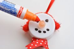 "These tea light snowman ornaments are really easy to make and they look ADORABLE! Turn on the tea light and the ""flame"" becomes the snowman's carrot nose!"