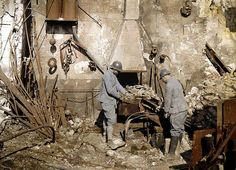 Two French soldiers work at a smith's hearth in a forge destroyed by grenades, 1917.