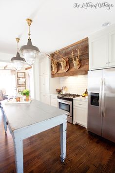 rustic light blue kitchen island table. Love the antlers above the stove too!!