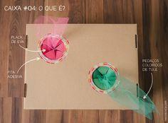 """Caixa #04: O que é? Fizemos círculos na tampa da caixa, decoramos com fita adesiva e criamos uma passagem usando EVA cortado para as crianças colocarem a mão sem conseguir ver o que tem dentro. Na caixa, uma cobra colorida feita de pedaços de tule amarrados. """"Será que são as tranças da Rapunzel?"""", perguntou uma das crianças durante a brincadeira. :)"""