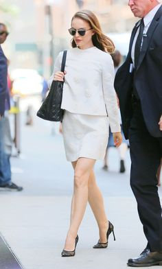 Natalie Portman wears an embroidered Valentino top-and-skirt set with Dior's Dior So Real sunglasses, an oversize tote, and sky-high stilettos.