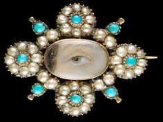 Lover's Eyes: How Eye Miniatures Became the Mood Rings of the Late 1700s | Vanity Fair    Yellow-gold brooch with border of 32 natural oriental half-pearls in a floral motif with eight small turquoise stones; brown right eye. Oval locket back with woven brown hair under glass. Circa 1820.