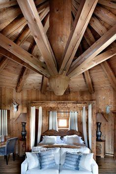 chalet en bois habitable, une jolie chambre à coucher avec murs en bois et plafond en bois